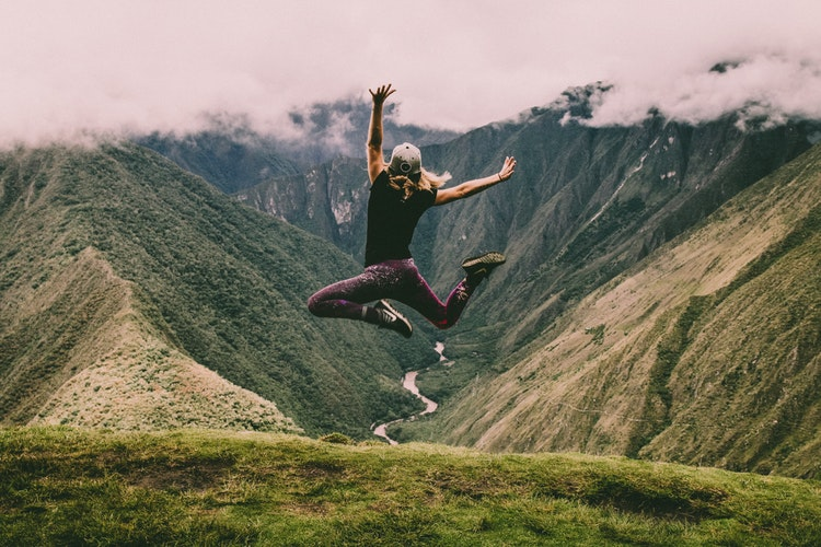 girl jumping at top of mountain