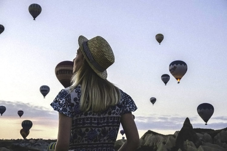 Woman looking out at hot air balloons.