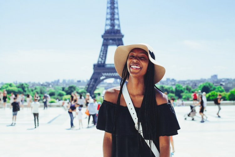 Woman smiling in front of the Eiffel Tower.
