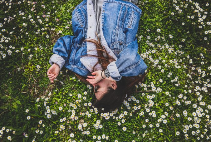 Woman laying in a field with flowers.