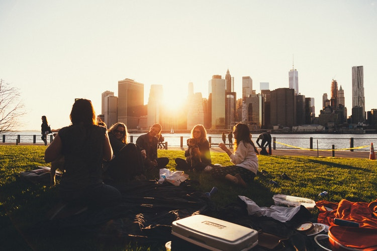 A group of women sitting in  park against a sun setting behind the city skyline.