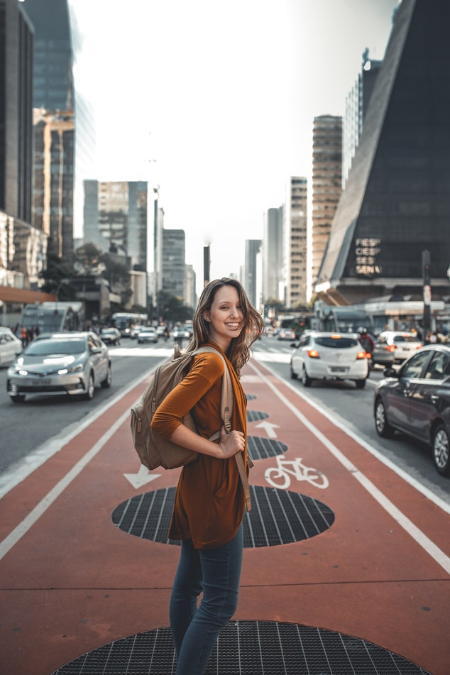 Woman standing in the middle of a city street.