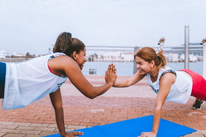 Two women working out outside together.