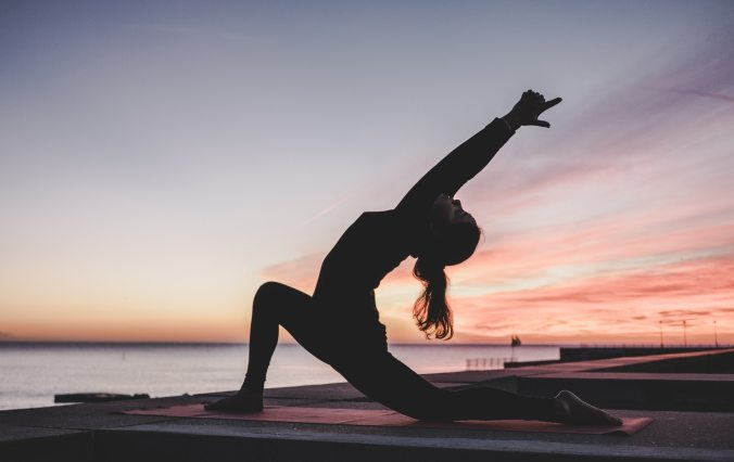 Woman doing yoga on a pier.