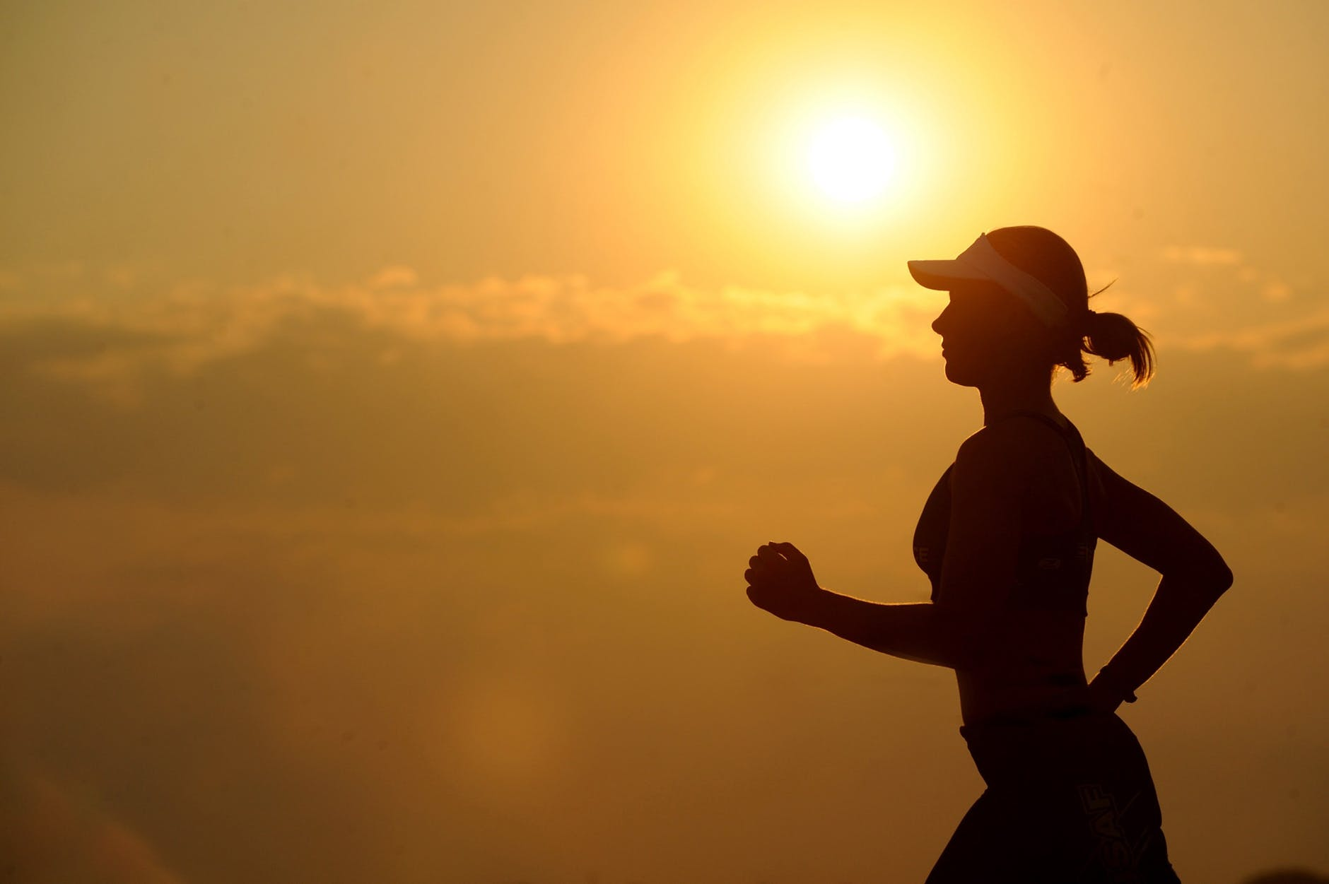 Woman's silhouette running against the sunrise